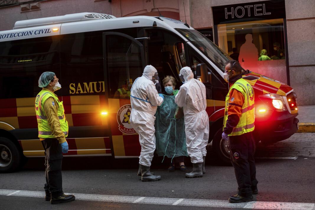En pasient i Madrid blir fraktet til hotell som midlertidig er gjort om til sengeplasser for pasienter.