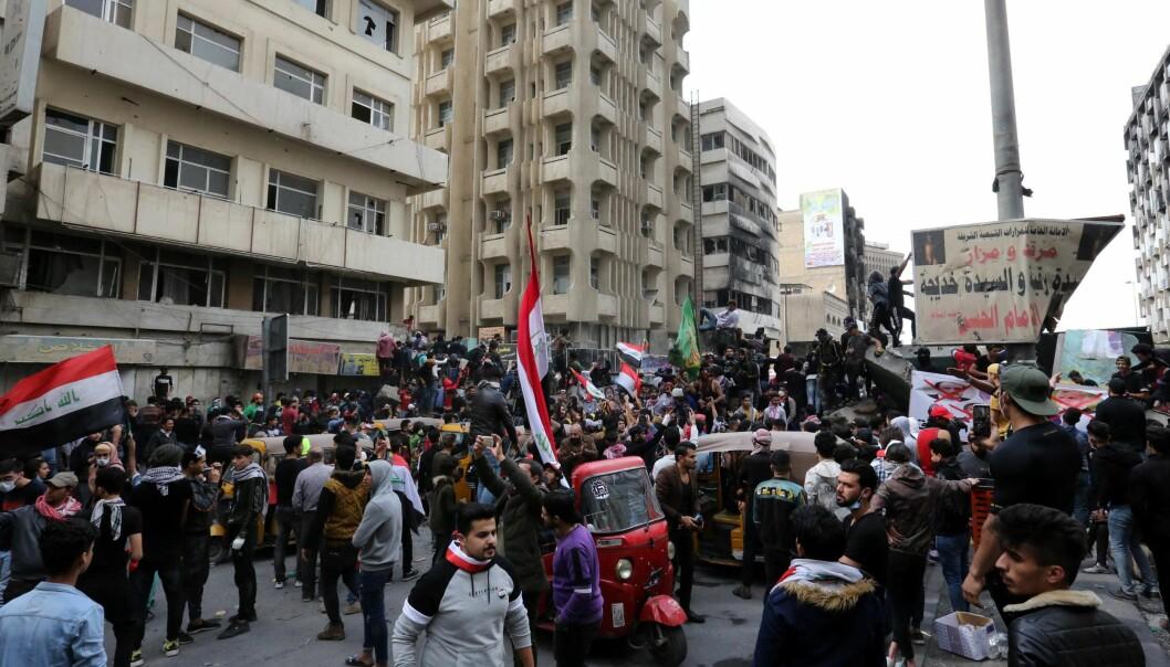 Demonstranter i Bagdad bærer irakiske flagg mens de fjerner veisperringer i hovedstaden. Bildet er tatt 1. mars.