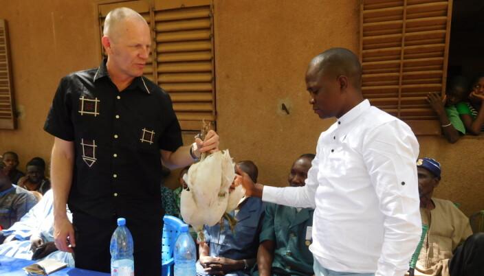 Haugsjå mottar ei høne i gåve i landsbyen Tambaga under eit besøk i 2019.