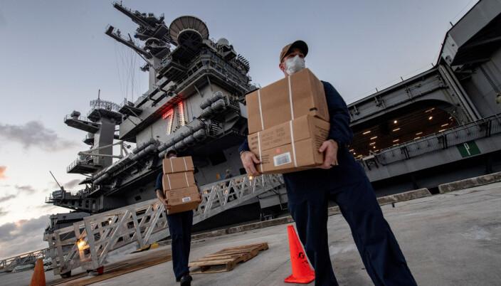 Besetningsmedlemmer ved USS Theodore Roosevelt bærer MRE- måltider til soldatene som har testet negativt for koronaviruset som er i karantene på et lokalt hotell på øya Guam den 7. april 2020.