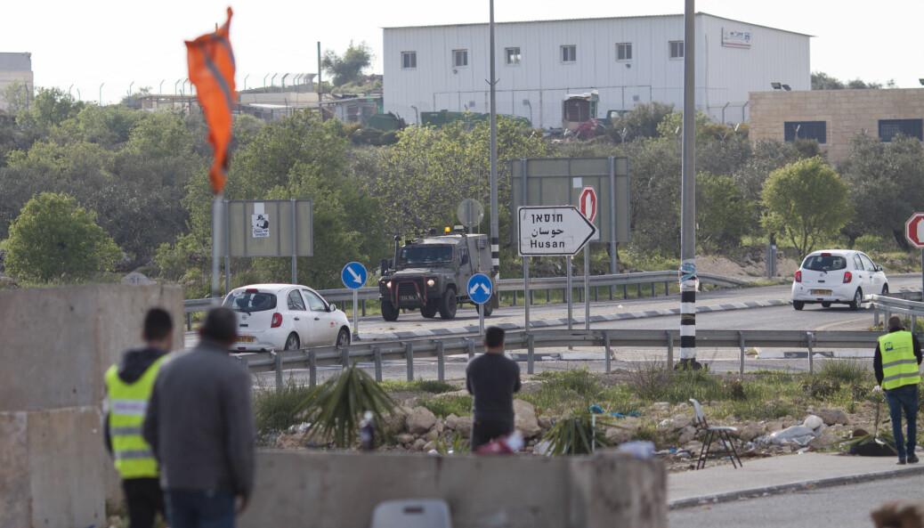 Israelske militærkjøretøy kjører forbi medlemmer av den lokale palestinske nødkomiteen i byen Husan nær Bethlehem. Byen er i ferd med å stenges for å hindre spredning av Covid-19.