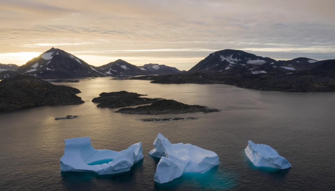 Store isberg flyter i havet i soloppgangen ved Kulusuk på Grønland. USA pumper nå penger inn i bygging av skoler, turisme og råvareindustri på øya. President Donald Trump uttrykte i fjor høst ønske om å kjøpe Grønland, men fikk blankt avslag.