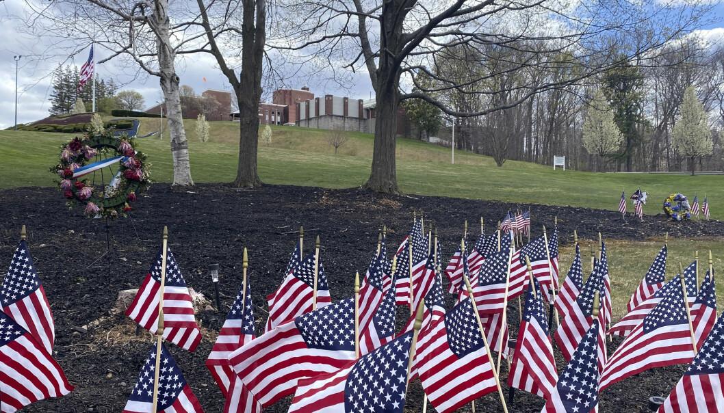 Flagg og blomsterkranser til minne om de avdøde veteranene utenfor pleiehjemmet i Holyoke. Utbruddet er trolig det verste ved en pleieinstitusjon i USA.