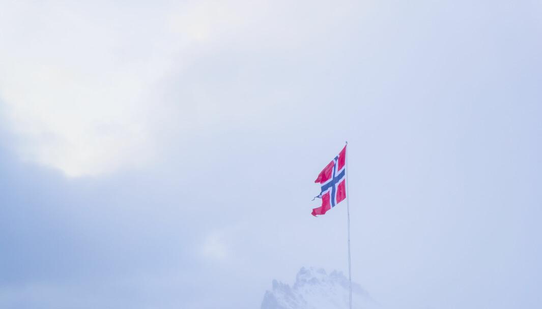 Det norske flagget vaier foran Schiertzegga ved Olonkinbyen på Jan Mayen i februar.