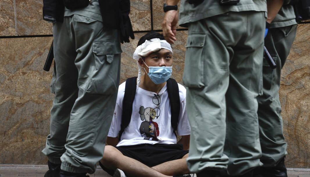 Opprørspoliti omringer en demonstrant i Hongkong etter at en svært kontroversiell sikkerhetslov ble vedtatt av kinesiske myndigheter.
