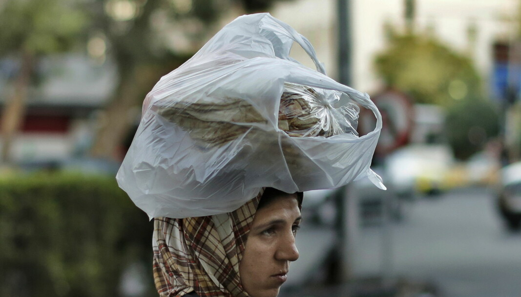 En syrisk kvinne bærer brød på hodet i hovedstaden Damaskus sommeren 2019.