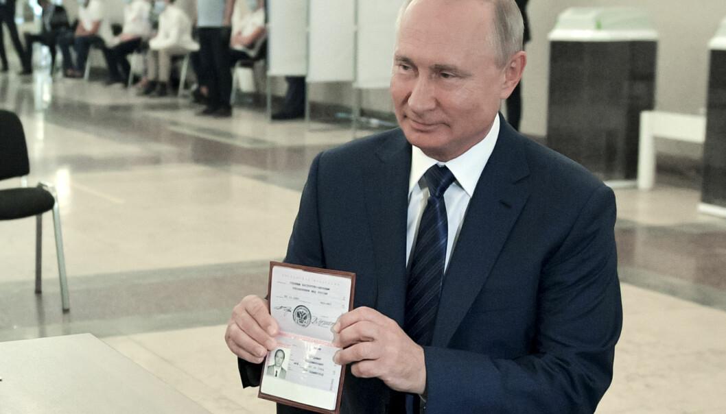 Russlands president Vladimir Putin viser frem passet sitt ved et stemmelokale i Moskva, Russland 1. juli.