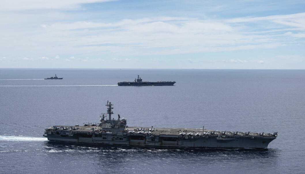 Hangarskipa USS Ronald Reagan (fremst) og USS Nimitz (i bakgrunnen) seglar saman i formasjon i Sørkinahavet måndag. Ekspertar åtvarar om at risikoen for militær konflikt mellom USA og Kina er større enn nokon gong, med stadig høgare spenning i Sørkinahavet.