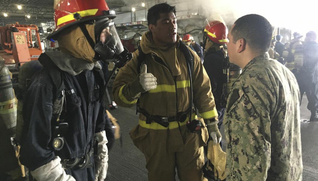 Dette bildet er sendt ut av U.S. Navy og viser brannpersonell og militært personell diskutere brannen.
