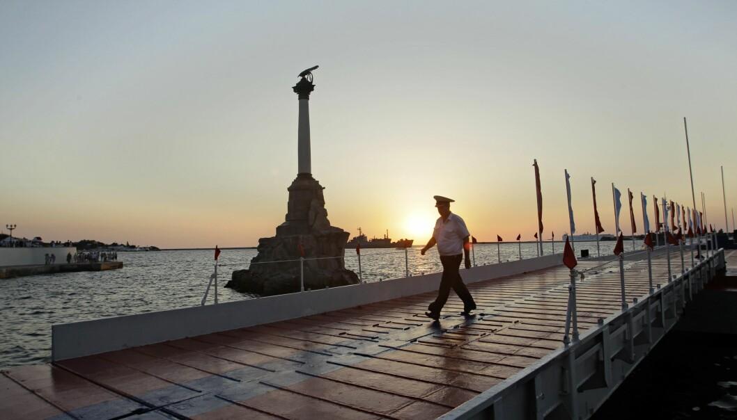 En offiser spaserer langs en av utstikkerne ved den russiske svartehavsflåtens hovedbase i Sevastopol.