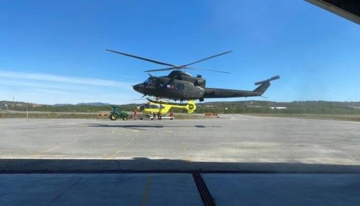 Norsk Luftambulanse AS' helikopter i bakgrunnen og Forsvarets Bell 412-helikopter i forgrunnen.