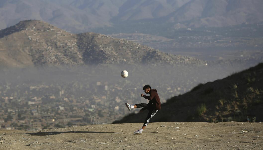 En ung afghansk gutt spiller fotball på en slette i utkanten av hovedstaden Kabul. Bildet er datert 21. juni.