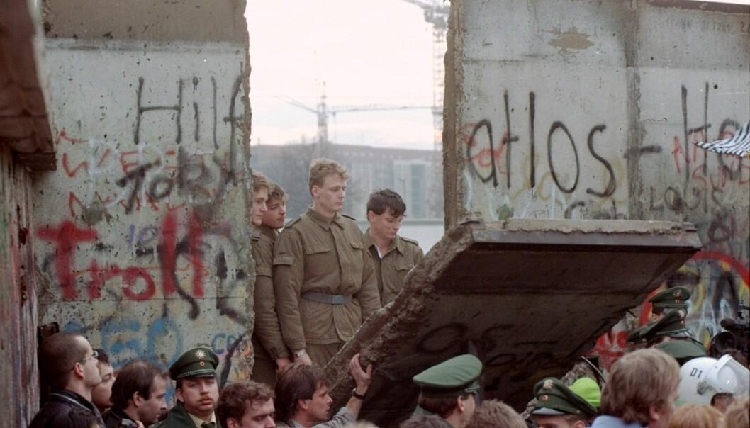 Seniorrådgiver Richard Utne begynner sine refleksjoner rundt teknologisk utvikling og samfunnssikkerhet ved Berlinmurens fall. Bildet viser østtyske grensevakter som har stilt seg i gapet etter en del av muren revet ned i nærheten av Brandenburg gate. Bildet er datert 11. november 1989.