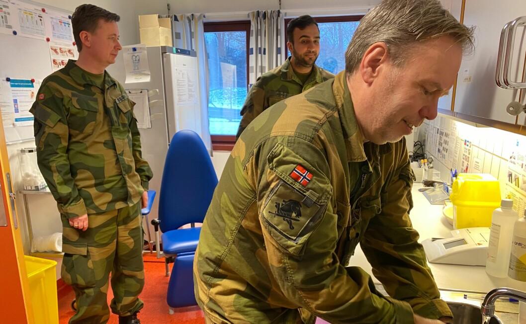 Sjefsveterinær Harald Wiik demonstrerer korrekt håndvask. Legene John Ødegård og Babar Ahmad følger med.