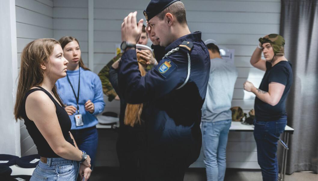 PRØVEPOST: Robin Skaar hjelper rekruttene til med å finne den riktige størrelsen i sjøforsvarets hodeplagg, beret.