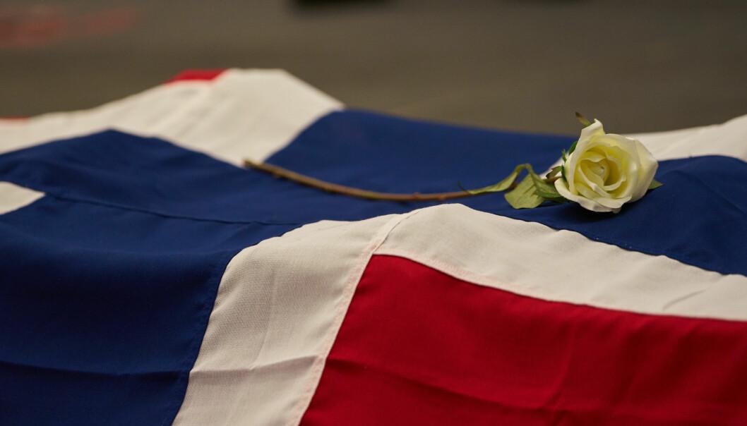 En hvit rose er lagt på det norske flagget til minne om Sindre Saltveit. Foto: Kystvakten.