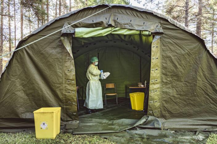 Telt med teststasjon for mistanke om koronasmitte vaskes ned etter bruk.