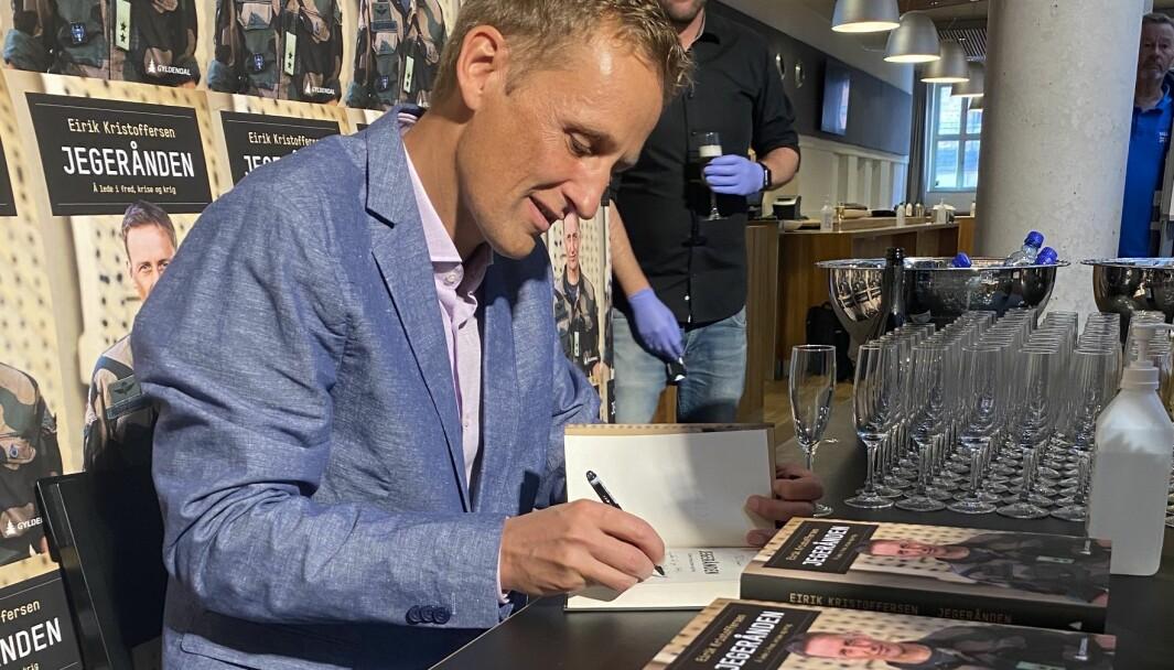 Eirik Kristoffersen signerer bøker under lanseringen på Gyldendalhuset.