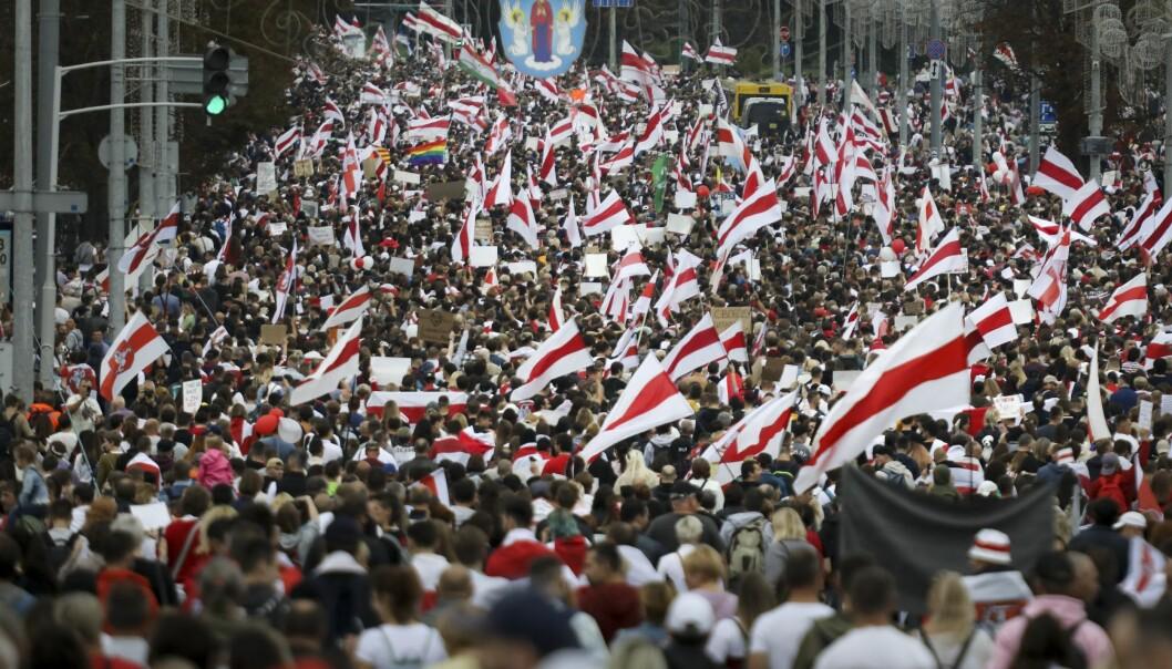 TITUSENER I GATENE: Demonstranter viftet med gamle hviterussiske flagg under en stor demonstrasjon i Minsk søndag. Det er fem uker siden de omfattende protestene tok til etter det omstridte presidentvalget i landet.
