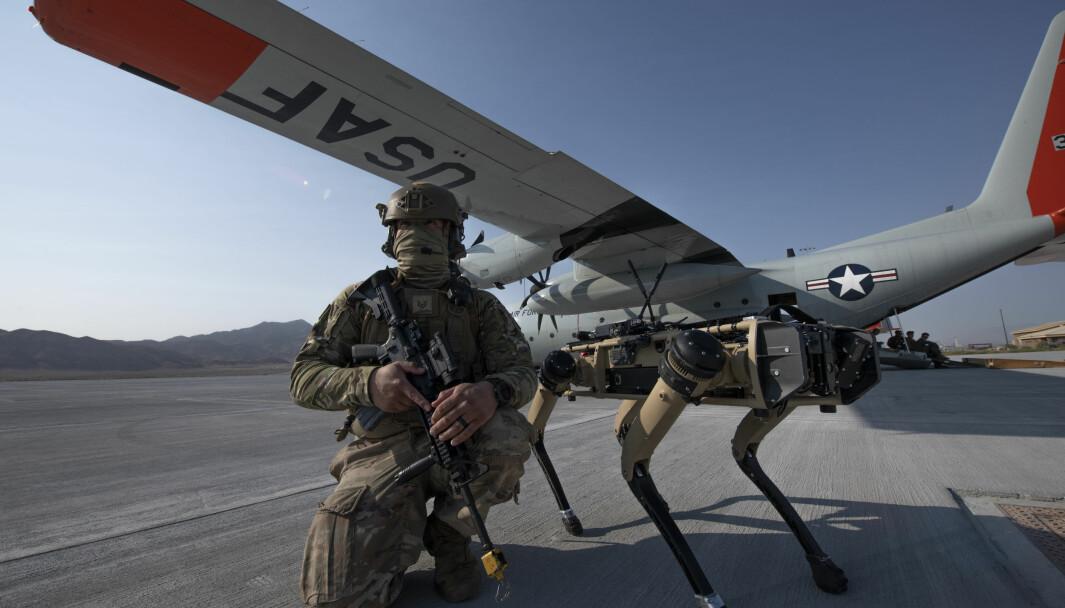 En amerikansk soldat sammen med en «robothund» under en øvelse i Mojave-ørkenen.