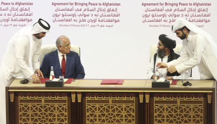 SIGNERER: I dette bildet fra 29. februar 2020, signerer den amerikanske utsendingen Zalmay Khalilzad, (t.v.), og Talibans Mullah Abdul Ghani Baradar en fredsavtale i Doha, Qatar. Det er denne avtalen som skisserte en uttrekning av amerikanske styrker innen 1. mai 2021.