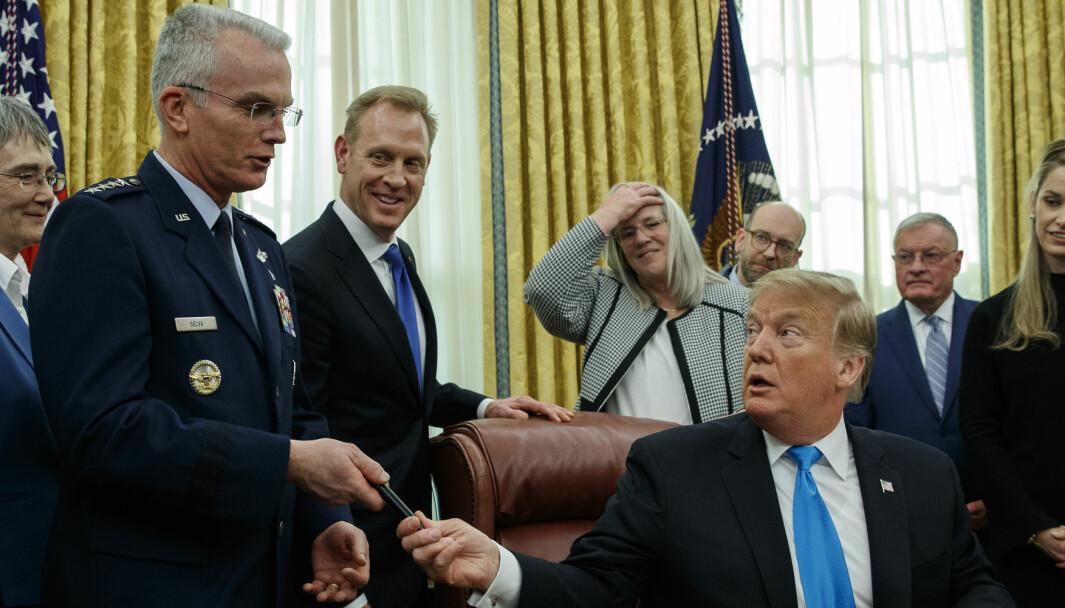 President Donald Trump gir en pen til daværende viseforsvarssjef general Paul Selva etter å ha signert «Space Policy Directive 4» i Det hvite hus 19. februar 2019.