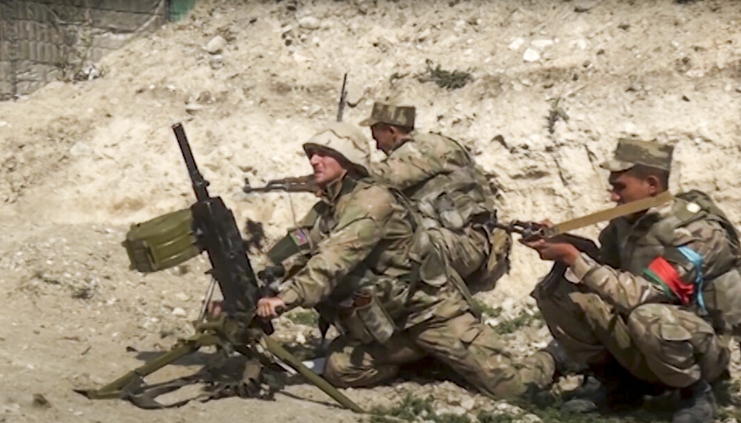 I dette bildet fra søndag 27. september avfyrer aserbajdsjanske soldater en automatisk granatkaster fra en av frontlinjene mot den selverklærte republikken Nagorno-Karabakh i Azerbaijan.