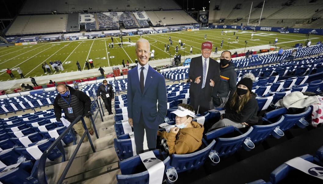 Tilhengere viser frem plakater av presidentkandidatene før en fotballkamp i USA.