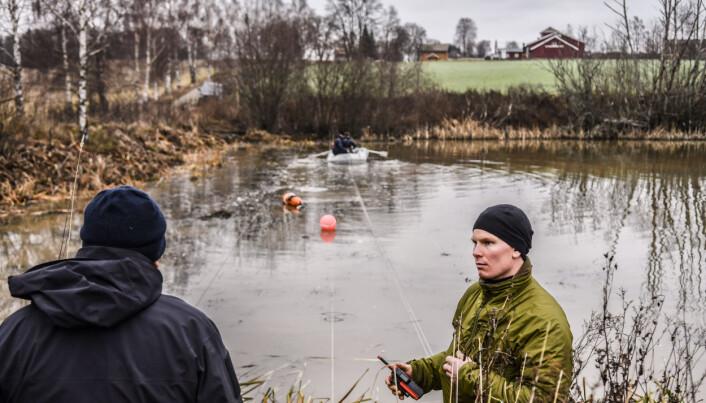 SYSTEMATISK: Operatørene strekker liner over dammen for å markere søkeområdet. I forgrunnen er kvartermester Emil Fadler Kvamme i samtale med politiet.
