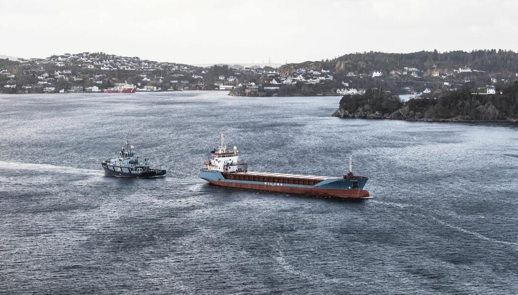 Lasteskipet «Wilson Parnu» som fikk motorstans og havnet i trøbbel sørvest for Sotra kjører nå under Askøybrua på veg mot Bergen. Slepebåten «Vortex» henger på og hjelper til med styringen.