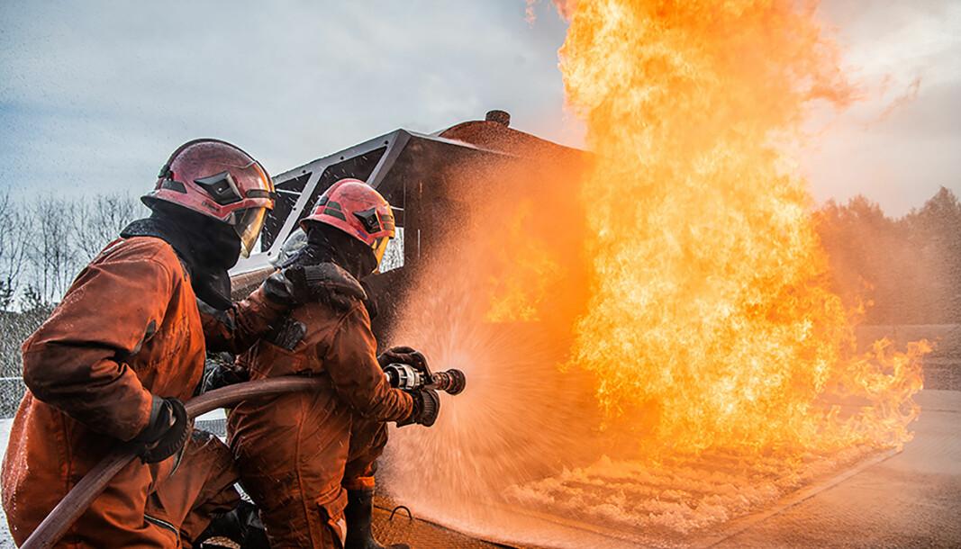 To soldater på røykdykkerkurs øver på å slukke en brann.