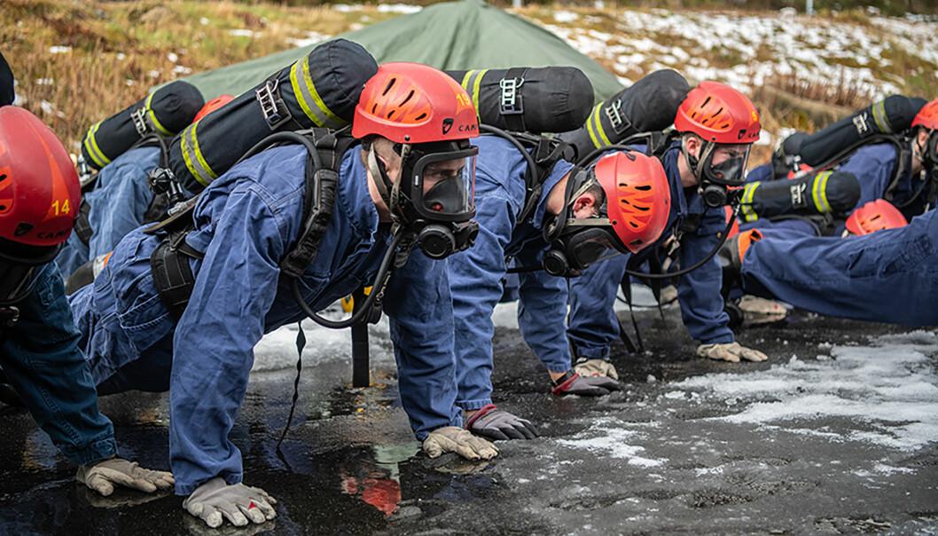 Soldater står i ferdigstilling med oksygentank på ryggen.