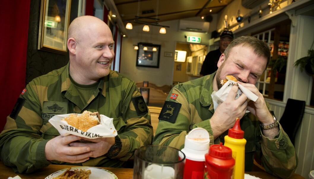 Geir Magne Trøyterud (t.v.) og Oddbjørn Dalsbø setter tennene i hamburgeren som kalles «Bjerkvikingen». Under militærøvelser øker omsetningen betydelig for Det lille kjøkken i Bjerkvik.