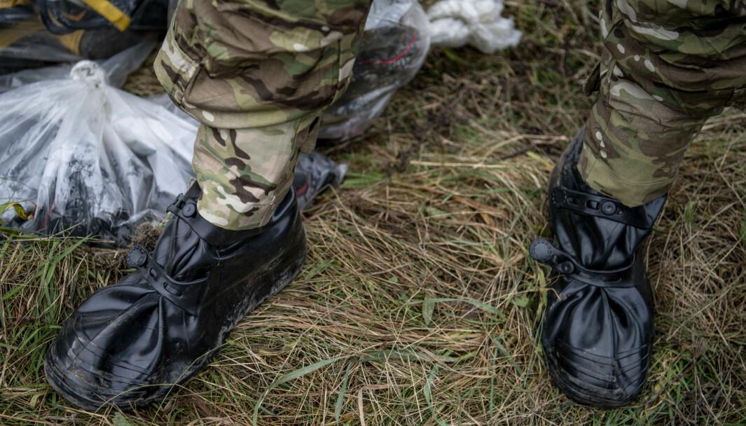 Danske helsemyndigheter og personell fra den danske hæren ikledd sikkerhetsutstyr.