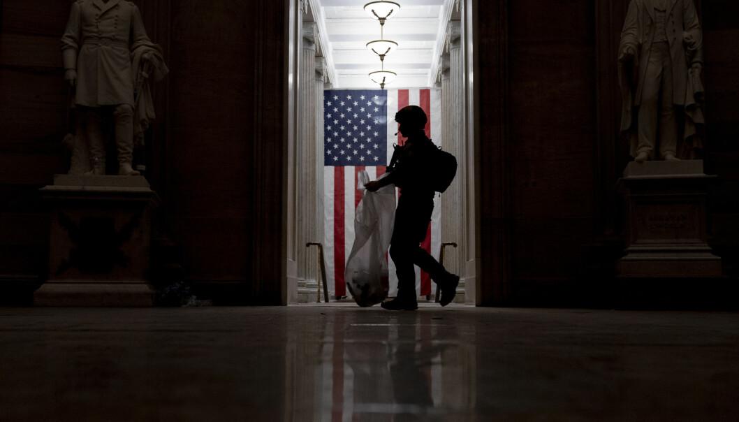En politibetjent rydder opp i de tidlige morgentimene torsdag, etter at demonstranter stormet Kongressen onsdag 6. januar.