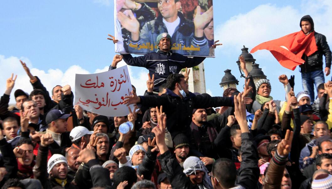 SJASMINREVOLUSJONEN: Demonstranter i Tunisia i januar 2011 foran et bilde av Mohamed Bouazizi, grønnsakshandleren som satte fyr på seg selv.