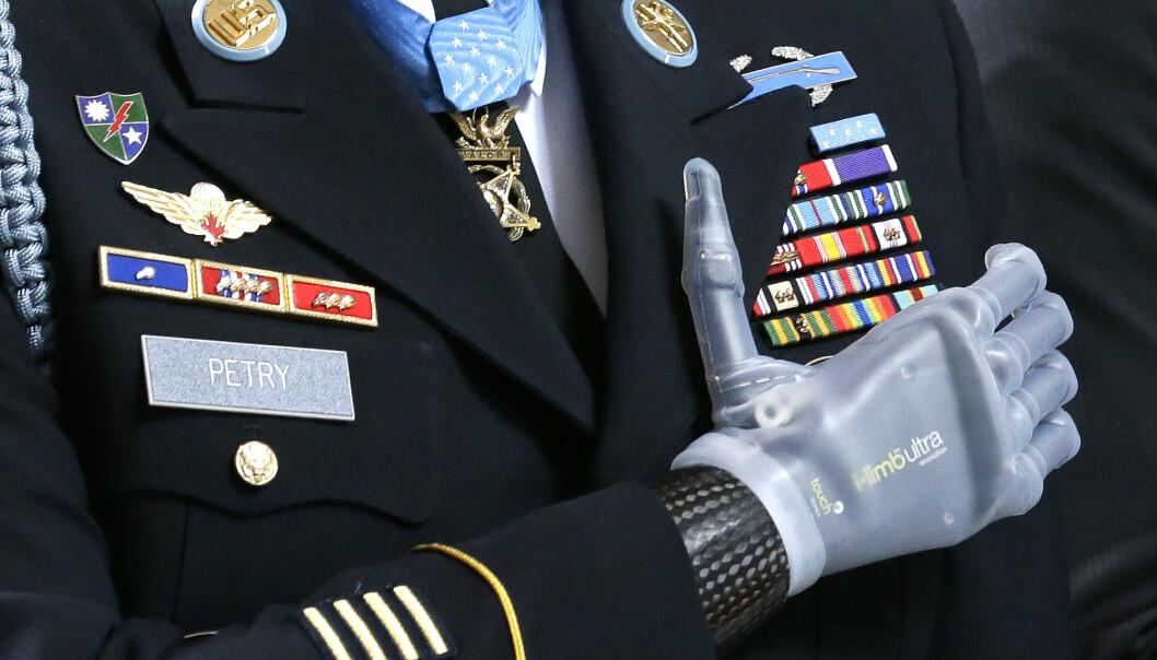 SÅRET I KAMP: Sersjant Leroy Petry holder seg til hjertet med sin håndprotese under en medaljeseremoni i Olympia i delstaten Washington i 2014. Petry mistet hånden i 2008, da han skulle kaste en fiendtlig granat vekk fra sine medsoldater under kamper i Afghanistan.