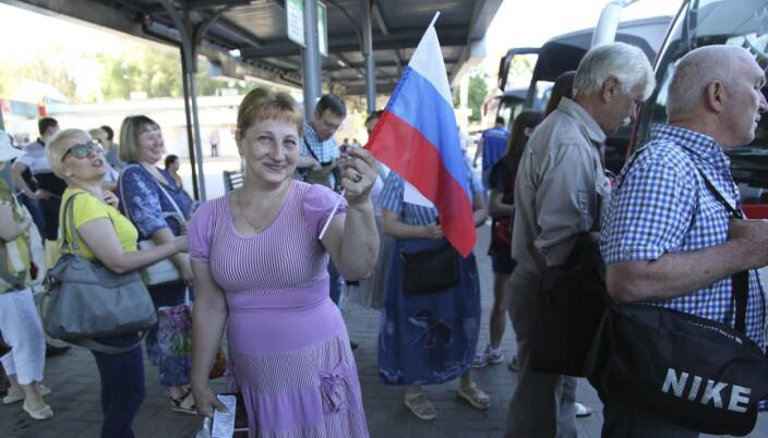 STATSBORGERSKAP: Russland har gitt russisk statsborgerskap til mange av innbyggerne i Donetsk. Denne kvinnen vifter med et russisk flagg, på veit til Russland for å stemme i folkeavstemningen endringer i den russiske grunnloven.