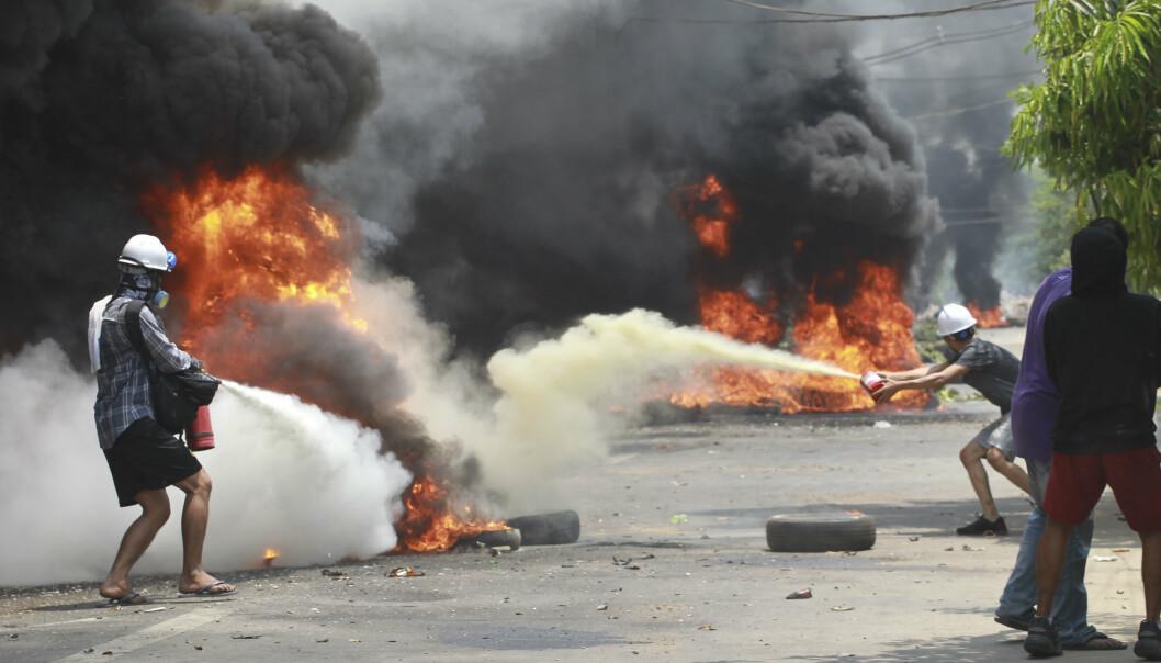 Demonstranter forsøke å slukke branner under en protest i Thaketa Township, søndag.