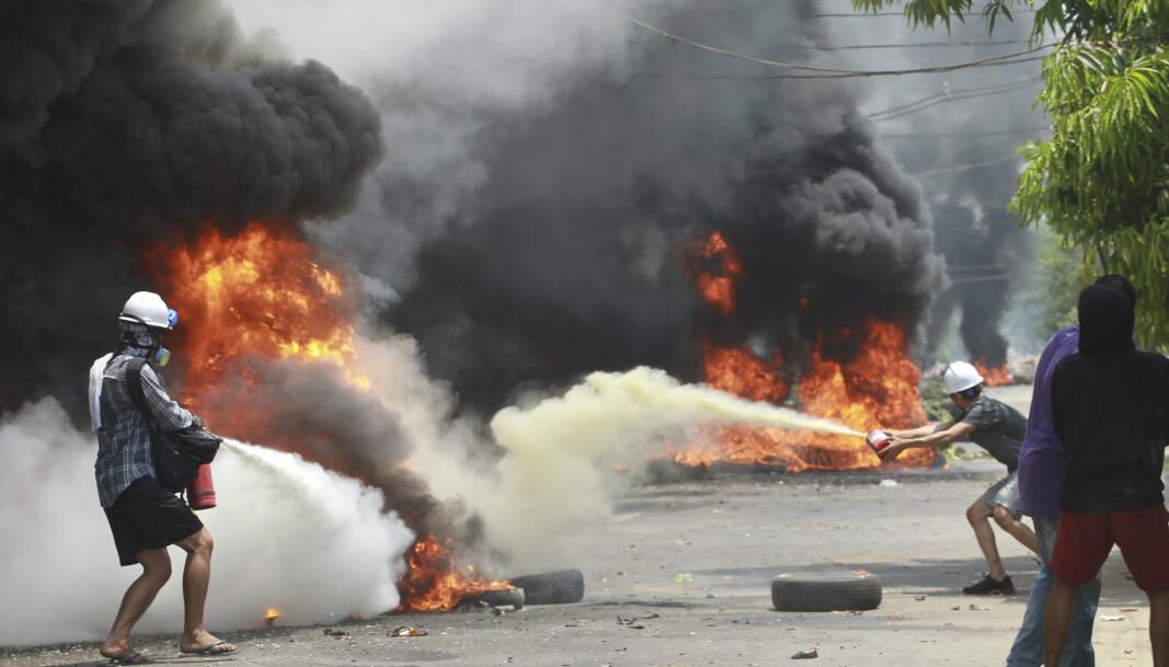 Demonstranter slukker flammer under en protest i bydelen Thaketa i Myanmars største by Yangon lørdag. En rekke mennesker skal ha blitt drept i sammenstøt med sikkerhetstjenestene rundt i landet i løpet av dagen.