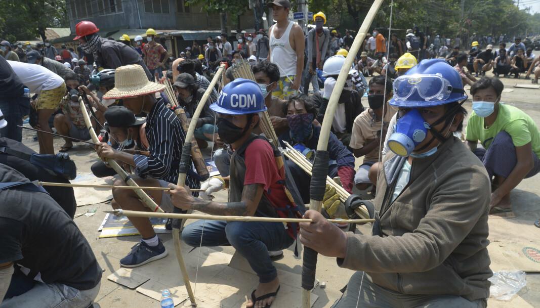 Kuppmotstandere væpnet med pil og bue i en konfrontasjon med politiet i bydelen Thaketa i Myanmar lørdag.
