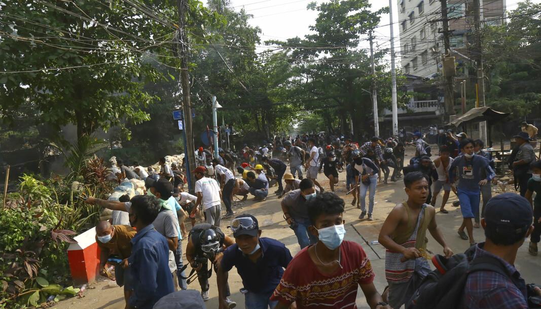 Opprørspoliti bryter opp en folkemengde i Yangon i Myanmar søndag.