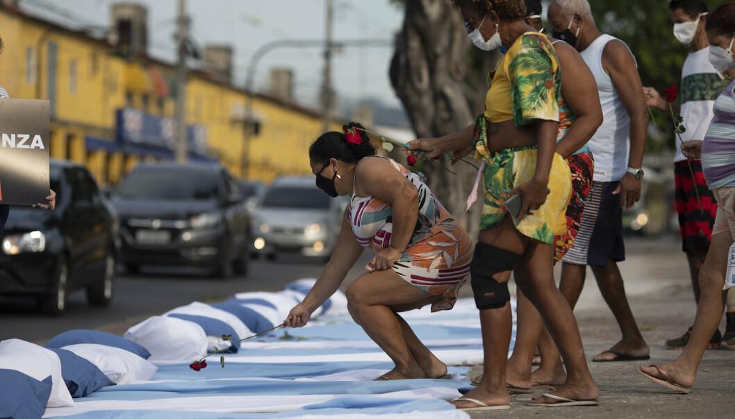 Demonstranter plasserer roser på madrasser som symboliserer koronapasienter under en protest i Rio de Janeiro mot regjeringens håndtering av pandemien.