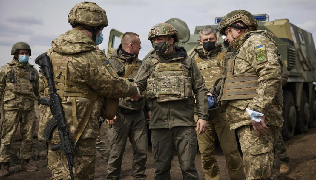 Situasjonen i Øst-Ukraina er spent, og tidligere denne uken var den ukrainske presidenten Volodymyr Zelenskyj (i midten) på besøk ved fronten. Russland avviser søndag at de har planer om å gå til krig mot nabolandet.
