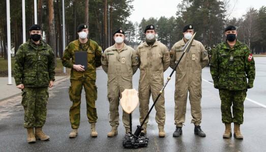 SPYD: Norsk og canadiske soldater med et trofé formet som et spyd.