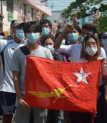 Demonstranter med flagget til partiet Nasjonalligaen for demokrati. Bildet ble tatt i Yangon søndag.