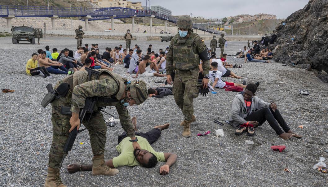 UTSLITT: Spanske soldater hjelper migranter som er utslitt etter å ha svømt rundt en molo fra Marokko til enklaven Ceuta. De fleste av dem blir nå sendt tilbake til Marokko.