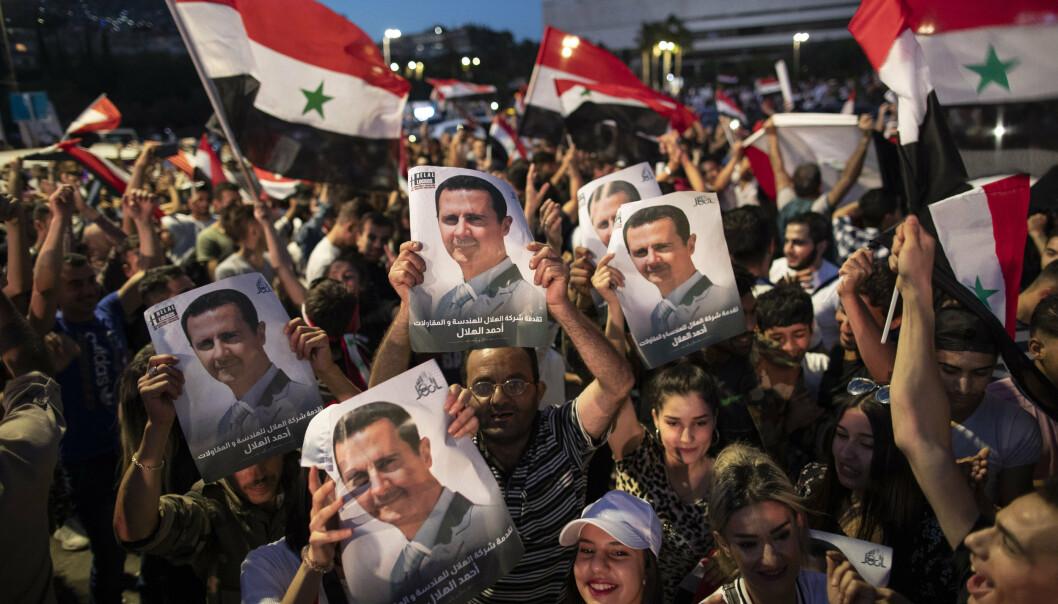 VALGT: Jublende tilhengere av Syrias president Bashar Assad holder opp bilder av sin president etter valget.