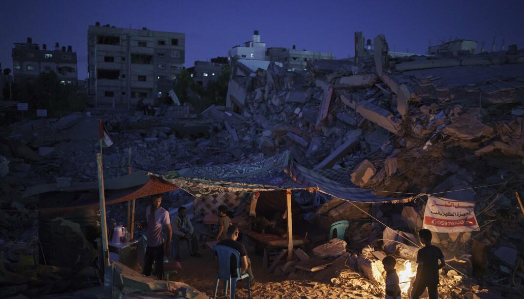 Palestinere sitter inne i et provisorisk telt bygget midt i ruinene til hjemmet deres.