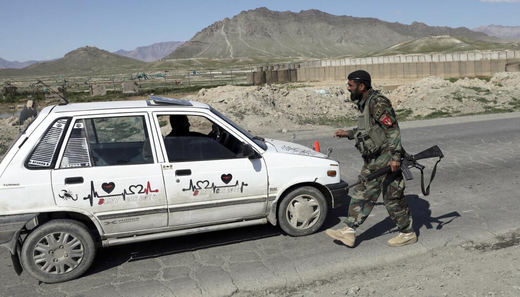 KABUL: En afghansk regjeringssoldat kontrollerer en bil utenfor Kabul. Samtidig rykker Taliban fram i flere distrikter.